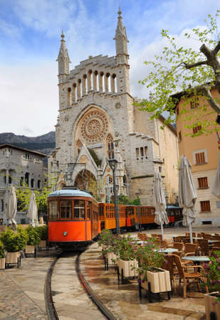 Old tram in the downtown of Soller in front of medieval gothic cathedral with huge rose window, Mallorca, Spain