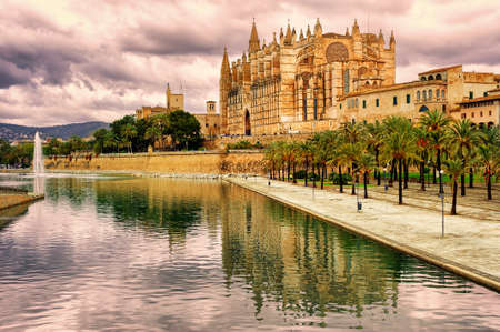 La Seu, the cathedral of Palma de Mallorca, reflecting in the water on sunset, Spain Фото со стока