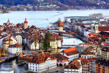 water town: Aerial view of the red tiled roofs of the old town of Lucerne, wooden Chapel bridge, stone Water tower, Reuss river and Lake Lucerne, Switzerland Stock Photo