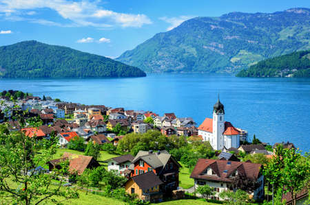 lucerne: Little swiss town with white gothic church on the shore of Lake Lucerne, Alps mountains, Switzerland