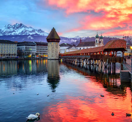 water town: Dramatic sunset over the old town of Lucerne, Chapel Bridge, Water tower and snow covered Pilatus Mountain, Switzerland