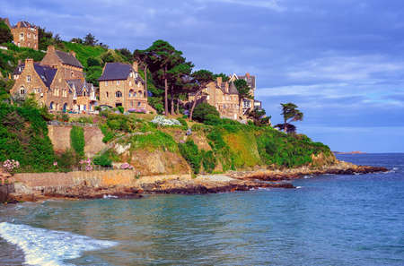 sea cliff: Traditional breton stone houses on a steep cape in English Channel, Brittany, France Stock Photo