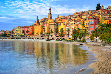 french: Sand beach beneath the colorful old town Menton on french Riviera, France