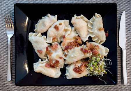 pierogi: Polish Pierogi stuffed dumplings served in traditional restaurant on a black plate and decorated with ham and green sprouts