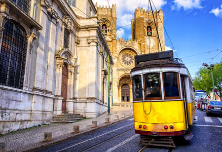 28: Historical yellow tram in front of the Lisbon cathedral, Alfama, Lisbon, Portugal