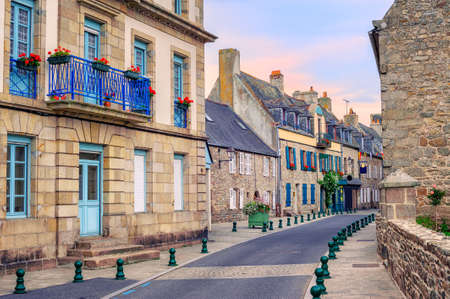 old city: Traditional french stone houses with blue windows decorated with red flowers in Roscoff, Brittany, France