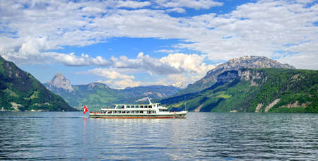 lucerne: Cruise ship in front of green alpine meadows and snow covered peaks of Alps mountains on Lake Lucerne, central Switzerland