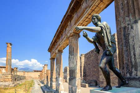 Ruins of the antique Temple of Apollo with bronze Apollo statue in Pompeii, Naples, Italy. Pompeii was destroyed by Vesuvius eruption in 79 AD.