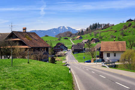 Traditional wooden houses in a little swiss village with snow Alps peak in background, central Switzerland 版權商用圖片