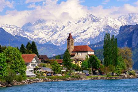 Brienz stad aan het Meer van Brienz door Interlaken, Zwitserland, met sneeuw bedekte bergen van de Alpen op de achtergrond