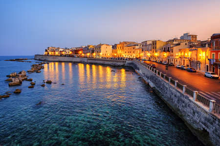 syracuse: Historical houses facing Mediterranean sea on the island Ortigia, the oldes part of Syracuse town, Sicily, Italy, on late evening