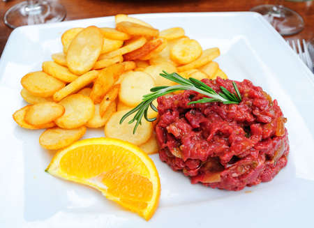 steak tartare: Steak tartare raw minced beef meat served with french fries potato chips and decorated with orange and rosemary Stock Photo