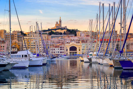 Yachts reflecting in the still water of the old Vieux Port of Marseilles beneath Cathedral of Notre Dame, France, on sunrise