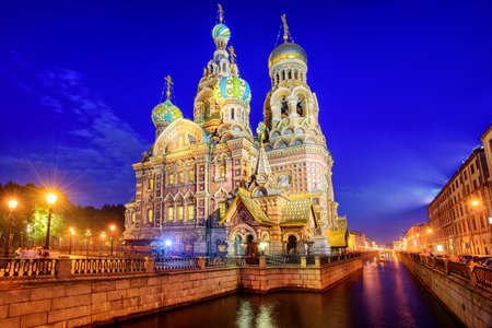 tourism russia: The orthodox Church of the Savior decorated with colorful onion domes on Griboyedov Canal illuminated at evening, St. Petersburg, Russia Stock Photo