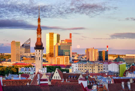 sunset: Skyline of Tallinn, Estonia, with old town church tower and modern buildings in background