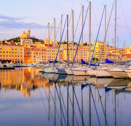 White yachts row reflecting in the still water of the old Vieux Port of Marseilles with Cathedral of Notre Dame, France, on sunrise Stock Photo