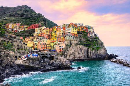 paisaje mediterraneo: Coloridas casas tradicionales en una roca sobre el mar Mediterráneo en espectacular puesta de sol, Manarola, Cinque Terre, Italia