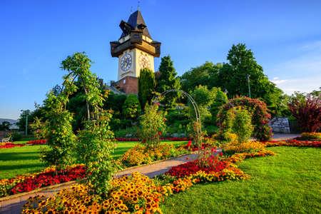 The medieval Clock tower Uhrturm in flower garden on Shlossberg hill, Graz, Austria