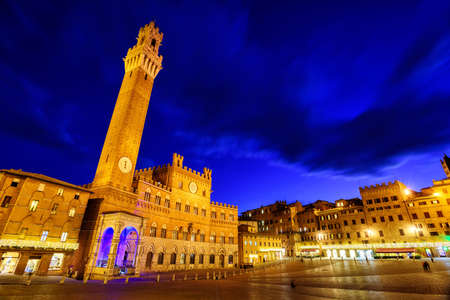 Piazza del Campo in the historic center of Siena, Tuscany, Italy, with Palazzo Pubblico and Torre del Mangia tower at late evening Editorial