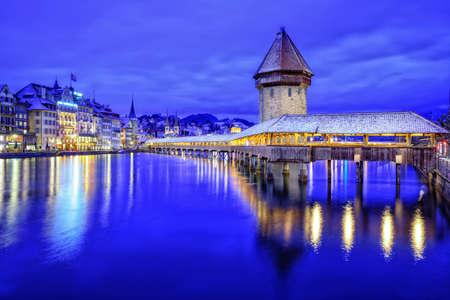 Luzern oude stad, Zwitserland, met houten kapel brug over Reuss rivier, de watertoren en promenade op een blauwe winteravond