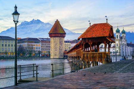 water town: Chapel Bridge, Water Tower and Mount Pilatus in the old town of Lucerne, Switzerland, in the early morning light