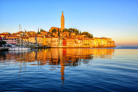 Historical Old Town of Rovinj, Croatia, reflecting in blue water of Adriatic sea on sunrise