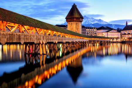 Hölzerne Kapellbrücke, Wasserturm und Pilatus in der Altstadt von Luzern, Schweiz, im späten Abendlicht