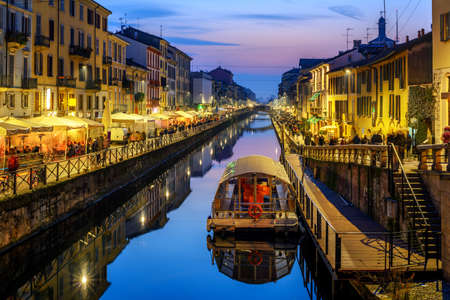 Milan city, Italy, Naviglo Grande canal is a popular illuminated in the late evening Фото со стока