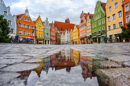 Traditional colorful gothic houses in the Old Town of Landshut, historical town in Bavaria by Munich, Germany, reflecting in a rain puddle Standard-Bild