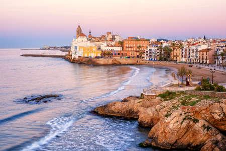 Playa de arena y casco histórico en el complejo mediterráneo de Sitges, cerca de Barcelona, Costa Dorada, Cataluña, España