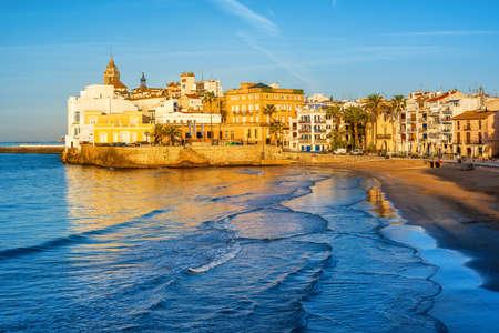 Playa de arena fina y casco histórico en el complejo mediterráneo de Sitges, cerca de Barcelona, Costa Dorada, Cataluña, España, a la luz de la mañana temprano Foto de archivo