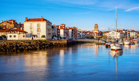 Traditional white houses in St Jean de Luz Old Town and port, Basque country, France, in sunset light