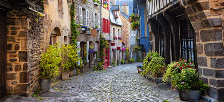 Dinan, traditional colorful houses on a cobbled street in medieval town center, Brittany, France Фото со стока
