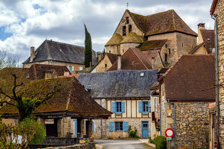 Creysse, a typical french village in Haut Quercy, Lot department, Martel, France, with traditional blue window shutters, brown brick buildings, tiled roofs and a roman church