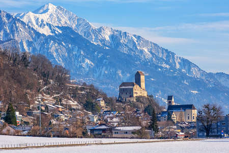 Sargans town with its famous medieval castle and snow Alps mountains peaks in background, St Gallen canton, Switzerland