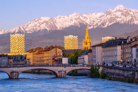 Grenoble city, France, view of historical town center with Isere river and snow covered french Alps mountains on sunset