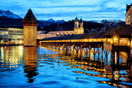 Lucerne, Switzerland, the Chapel bridge in the Old town reflecting in Reuss river in the late evening blue light 版權商用圖片