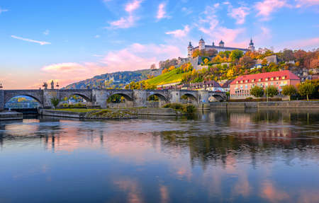 Wurzburg, Bavaria, Germany, view of the Marienberg Fortress and the Old Main Bridge reflecting in river on colorful sunrise 版權商用圖片