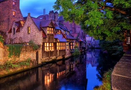 Traditional medieval houses on a canal in historical Bruges Old Town center, Belgium.