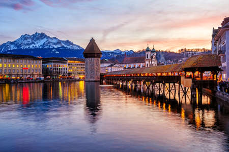 Lucerne, Switzerland, the wooden Chapel bridge in historical Old town and Mount Pilatus reflecting in Reuss river on dramatical sunset