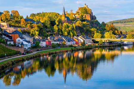 Medieval Saarburg town reflecting in Saar river on a sunny autumn day, Saarland, Germany