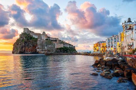Historische aragonesische Burg auf einem Felsen im Mittelmeer, Insel Ischia, Golf von Neapel, Italien, im dramatischen Sonnenaufgangslicht Standard-Bild