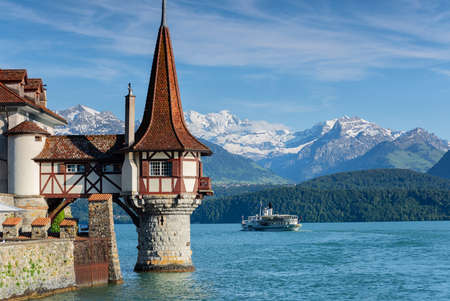 Lac de Thoune, Suisse, bateau de croisière passant entre le magnifique château d'eau et les montagnes des Alpes bernoises couvertes de neige Banque d'images