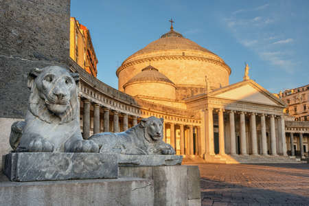 Naples, Italy, view of Basilica Reale Pontificia San Francesco da Paola church on Piazza del Plebiscito, main square of the city, and stone lion sculptures on sunrise Редакционное