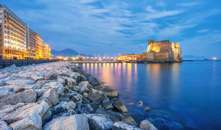Castel dell Ovo (Egg castle) in Naples, Italy, view from the seaside quay in blue evening light 新聞圖片