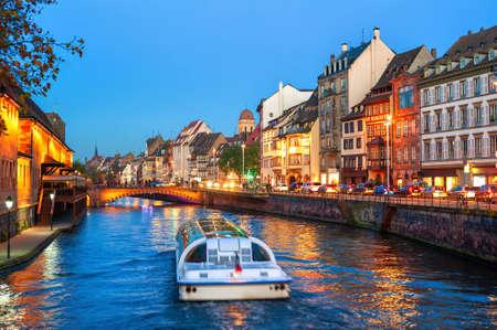 Ein touristisches Boot auf einem historischen Kanal in der Altstadt von Straßburg, Elsass, Frankreich
