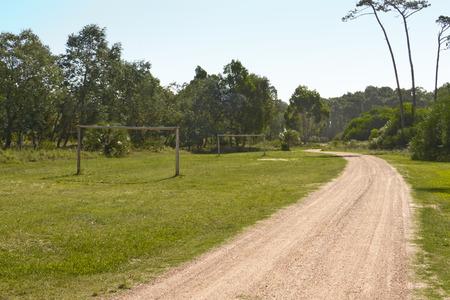 AFICIONADOS: campo de fútbol amateur con metas de madera cerca de una carretera.