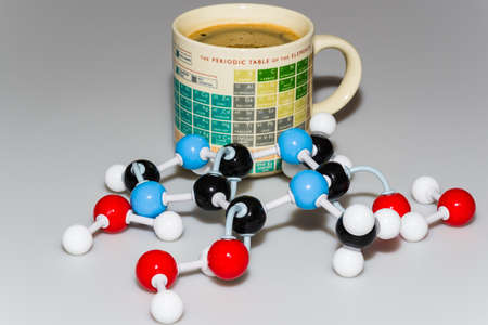 caffeine: Caffeine and water molecules in front of a Periodic table coffee mug on white-gray background