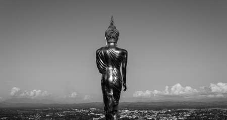 Black and white stand gold buddha of cityscape photo