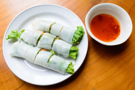 cuon: Spring rolls with vegetables on a white plate, wood background Stock Photo